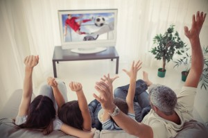 Family cheering and watching the world cup at home in the living room