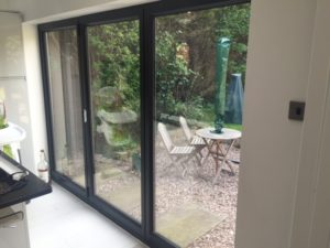This image shows anthracite bi fold doors with noblinds fitted to them